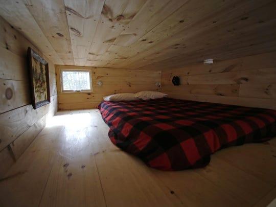 Sunlight illuminates the bedroom loft of a tiny house rental in Croydon, N.H.