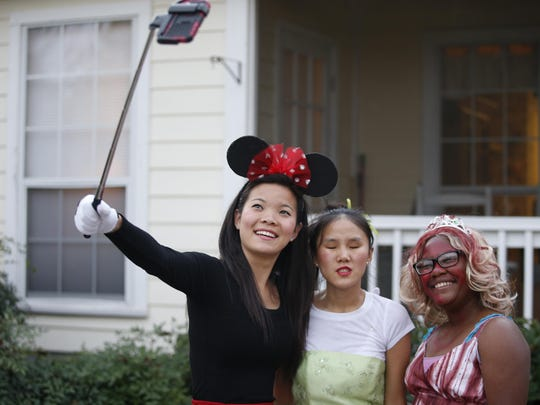 Julia Kadzis, from left, her adopted sister Melody Kadzis, and Destinee Germany, take a selfie together during a Halloween party hosted by a parent of a student who attends the Florida School for the Deaf and Blind, where they all met.