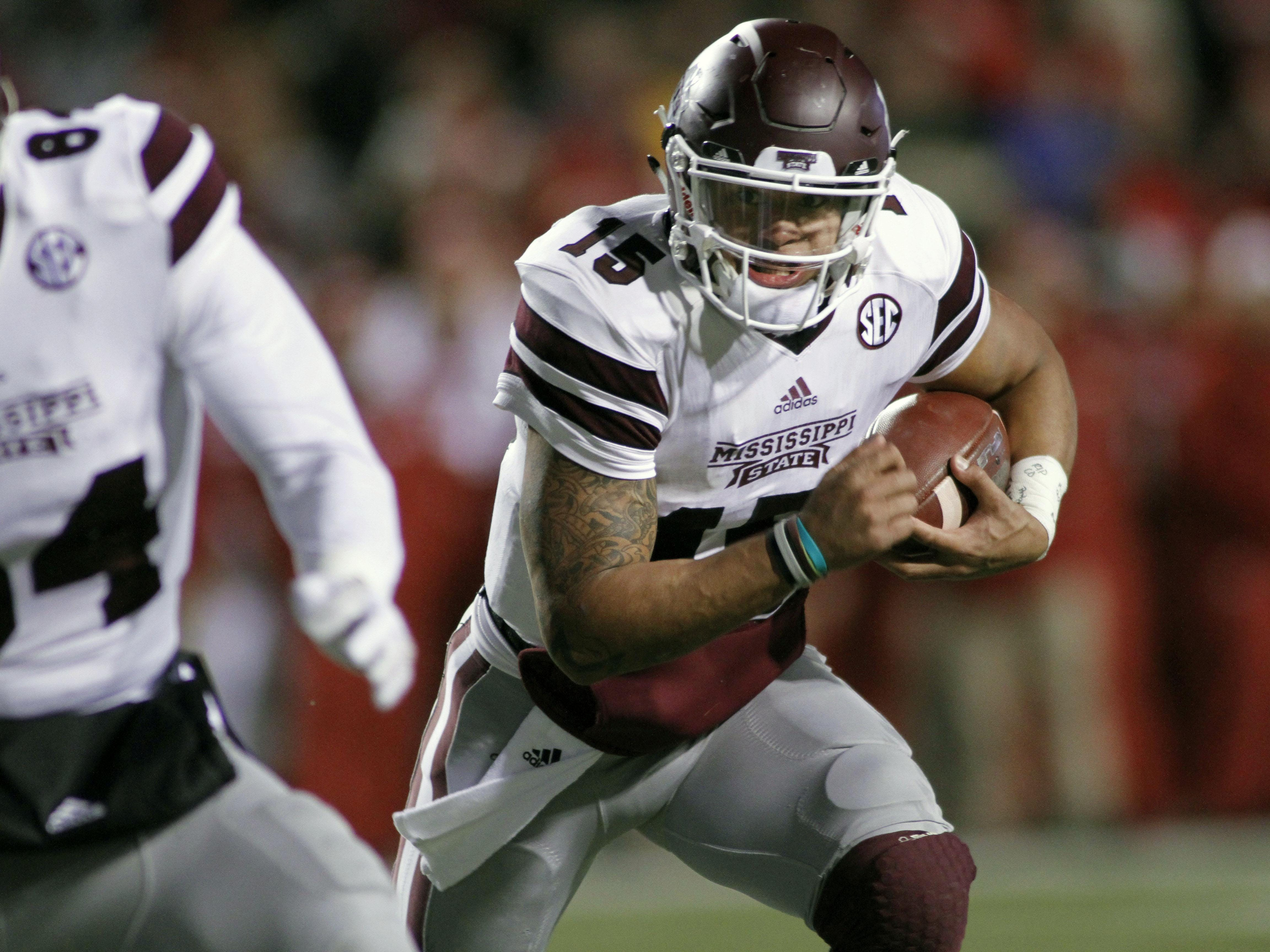 Mississippi State's Dak Prescott (15) keeps the ball and runs during the the first half against Arkansas on Saturday in Fayetteville.