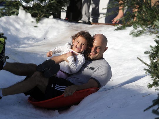Jim Feo and his daughter Brooke enjoy a slide on the snow slope at the Holiday Festival of Lights in Cape Coral.