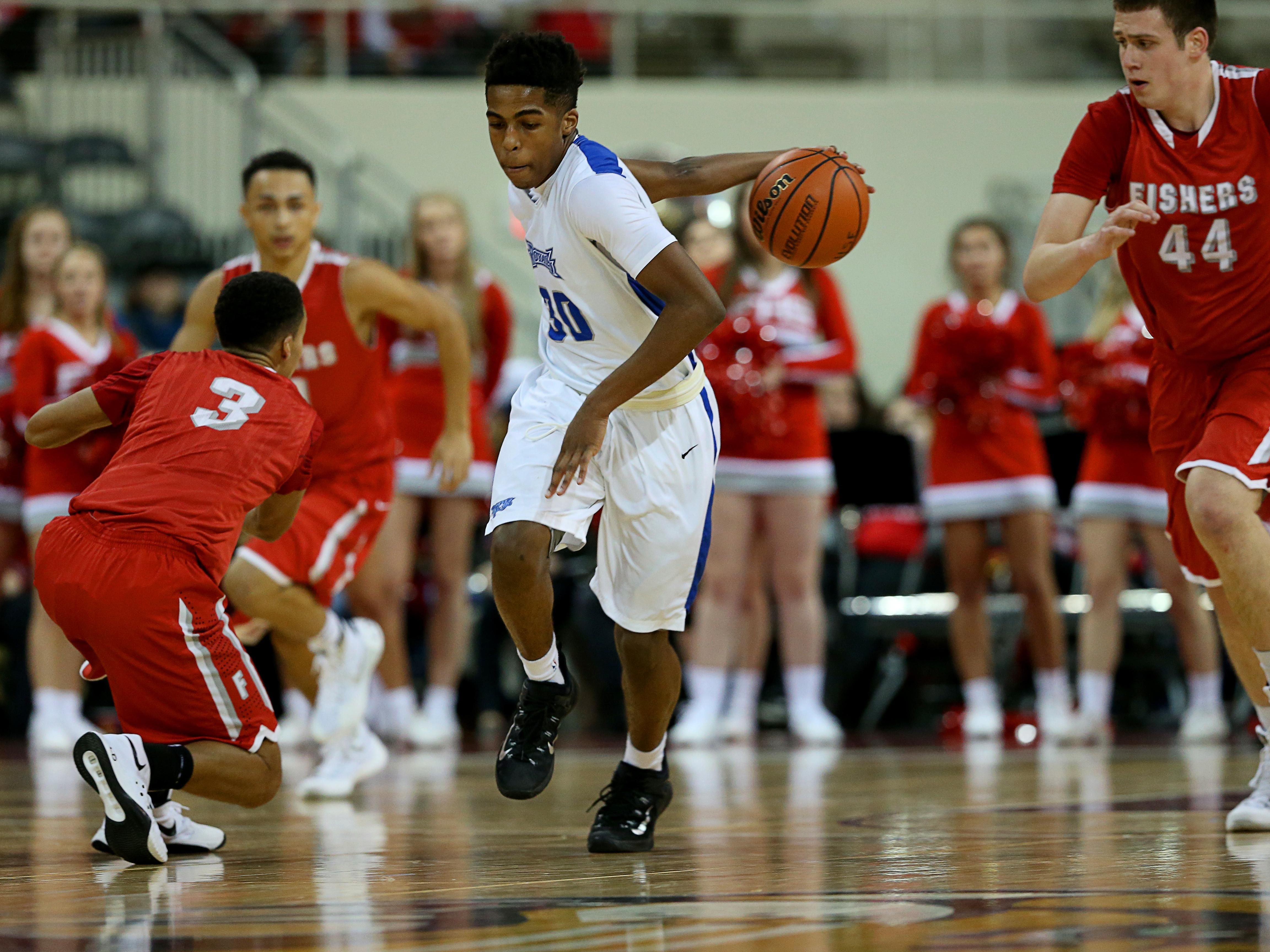 Hamilton SoutheasternÕs Noah Smith (30) goes behind his back on a fast break against Fishers at the Indiana Farmers Coliseum on Dec. 18, 2015.