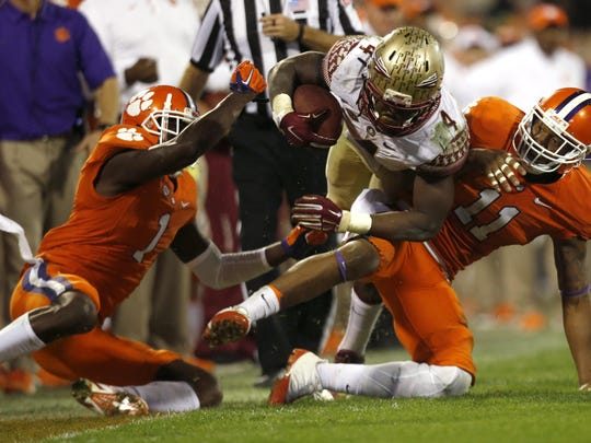 FSU's Dalvin Cook is tackled by Clemson's Jayron Kearse, left, and Travis Blanks during their game in November. Clemson won 23-13.