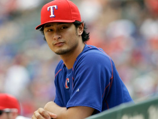 FILE - In this Sunday, Aug. 30, 2015 file photo,Texas Rangers pitcher Yu Darvish of Japan watches from the dugout during a baseball game against the Baltimore Orioles in Arlington, Texas. Yu Darvish says he has never been involved in gambling activities, but otherwise isn't commenting on a Major League Baseball investigation after the arrest of his younger brother in Japan. Darvish issued a statement Tuesday, Jan. 19, 2016 through his agent that says he understands MLB must conduct an investigation. But the Texas Rangers pitcher says he's certain they will find he had no involvement whatsoever. (AP Photo/LM Otero, File)