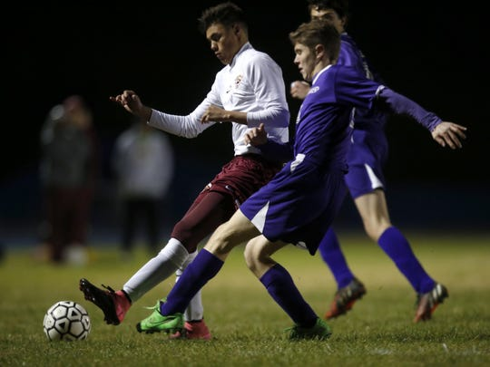 Florida High'€™s Nick Milligan dribbles past two Marianna defenders during their District Semifinal game at Rickards High School on Wednesday.
