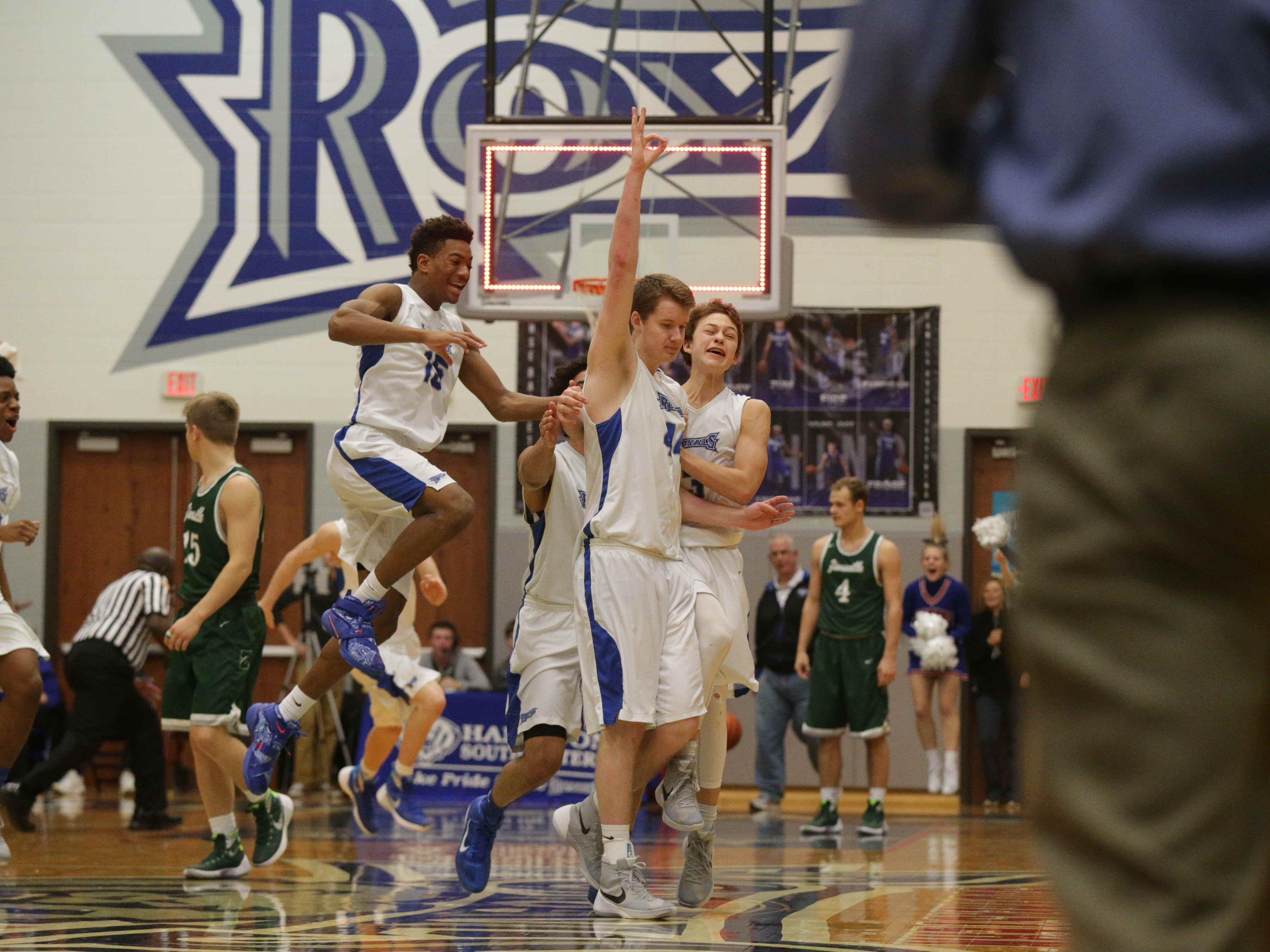 The Royal's #44, Brennan Schofield, center, celebrates after hitting a three point shot at the buzzer for the win, Friday January 22nd, 2016. Hamilton South Eastern VS Zionsville at HSE. Royals win 48-47. #15 Greg Miller, #42 Zach Gunn (behind), #3 Jack Davidson, right.