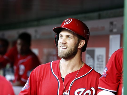 In this photo taken Sept. 19, 2015, Washington Nationals right fielder Bryce Harper (34) smiles in the dugout after hitting a two-run homer during a baseball game against the Miami Marlins at Nationals Park in Washington. Harper is a lot of things, namely the Washington Nationals' best player and the reigning National League MVP. One thing he's not is a leader. Harper arrived at Nationals spring training early and quietly took his place in the corner of the clubhouse with Ryan Zimmerman, Jayson Werth and Danny Espinosa. Even after being a unanimous MVP selection, the 23-year-old Harper would rather leave the leadership to those veterans. (AP Photo/Alex Brandon)