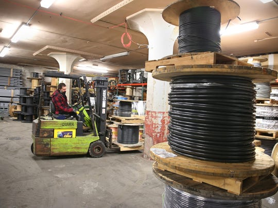 Doug Chase uses a forklift to move large rolls of wire in the warehouse at Kovalsky Carr Electric Supply Company in downtown Rochester Thursday, Feb. 25, 2016.