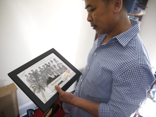Nhan Nguyen, a Vietnamese refugee who has settled in Tallahassee, holds a photo of his family reunited in the U.S.