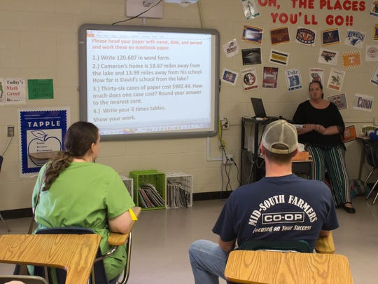 Corey and Kathleen Johnson listen to Sharon McIlwain teach a math class at North Parkway Middle School.