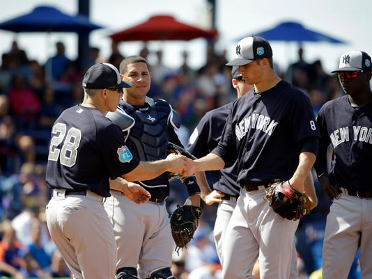 FILE - In this March 9, 2016, file photo, New York Yankees pitcher James Kaprielian, right, hands the ball to manager Joe Girardi as he is removed during the fifth inning of an exhibition spring training baseball game against the New York Mets in Port St. Lucie, Fla. Girardi wore No. 27 when he took over the job, since the franchise was chasing its 27th World Series title. The Yanks got that championship in 2009, and now Girardi wears No. 28. (AP Photo/Jeff Roberson, File)