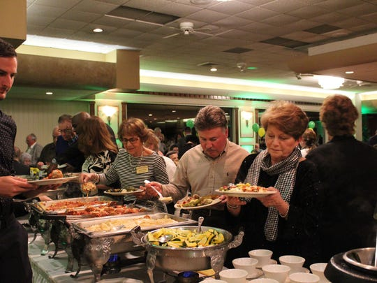 Guests line up along the buffet to try the dandelion dishes.