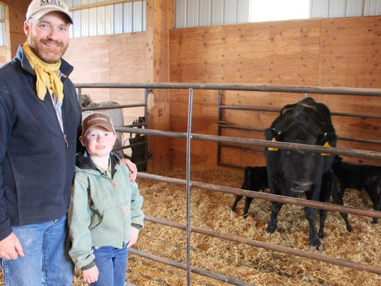 Iain McGregor and his son, Rial, pose beside cow 3202