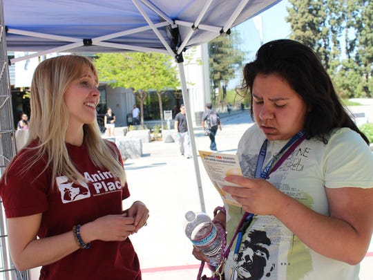 Stephanie Bain talks to a Fresno State student at the