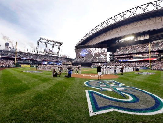 Oakland Athletics and Seattle Mariners players and coaches line the infield before the Mariners' home-opener baseball game Friday, April 8, 2016, in Seattle. (AP Photo/Elaine Thompson)
