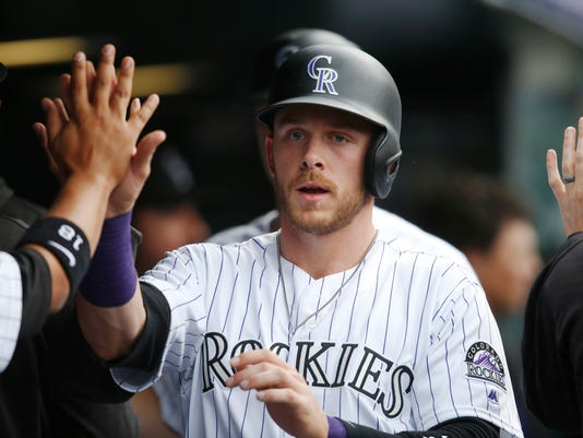 Colorado Rockies' Trevor Story is congratulated by teammates after scoring on a two-run double by Carlos Gonzalez off San Francisco Giants relief pitcher Hunter Strickland during the eighth inning of a baseball game Thursday, April 14, 2016, in Denver. Colorado won 11-6. (AP Photo/David Zalubowski)