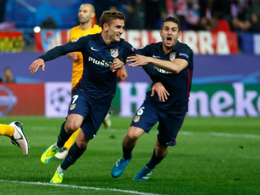 Atletico's Antoine Griezmann, left, and Atletico's Koke Resurreccion celebrate after Griezmann scored 2-0 during the Champions League 2nd leg quarterfinal soccer match between Atletico Madrid and Barcelona at the Vicente Calderon stadium in Madrid, Spain, Wednesday April 13, 2016. (AP Photo/Francisco Seco)