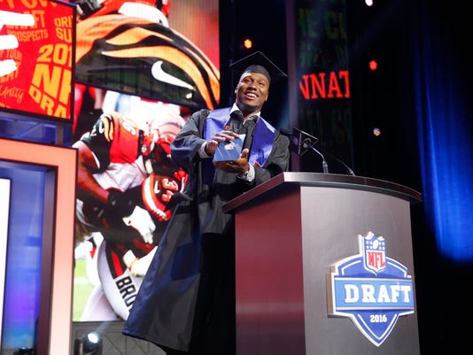 Former Walter Payton Men of the Year Carlos Dunlap announces that the Cincinnati Bengals selects Utah State's Nick Vigil as the 87th pick in the third round of the 2016 NFL football draft, Friday, April 29, 2016, in Chicago. (AP Photo/Charles Rex Arbogast)