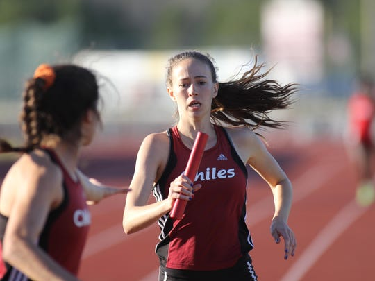 Chiles senior Emma Tucker makes a baton pass to sophomore Ana Wallace at an early-season meet. Tucker and Wallace are big threats at the state meet this weekend in the 1600.
