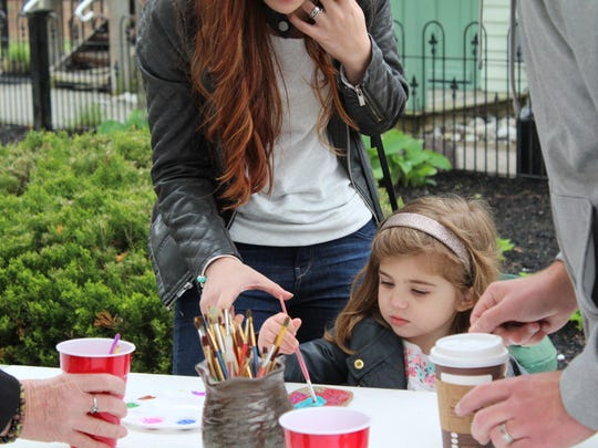Sofia Vespe, 2, paints an ornament with the help of her parents Angela and Michael Vespe.