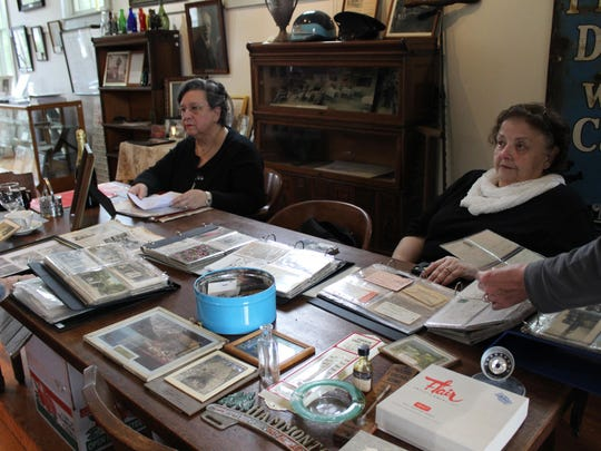 Angela Donio (left) and Dottie Orlandini sit behind the table holding some of their collections that were on display during an open house at the Hammonton Historical Society.