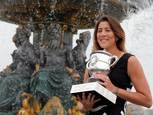 Spain's Garbine Muguruza poses with the French Open tennis trophy during a photocall at Concorde Plaza in Paris, Sunday June, 5 2016. Muguruza defeated Serena Williams of the U.S. in their final match of the French Open tennis tournament at the Roland Garros stadium. (AP Photo/Francois Mori)