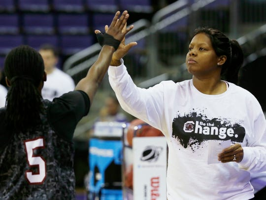 FILE- In this March 22, 2014, file photo, South Carolina assistant coach Nikki McCray, high-fives South Carolina guard Khadijah Sessions during practice at the NCAA women's college basketball tournament in Seattle. McCray was part of the 1996 U.S. women's basketball team. Their success has had a lasting impact on the game in many levels, sparking the launch of two professional leagues and inspiring players at the college and high school levels. (AP Photo/Ted S. Warren, File)