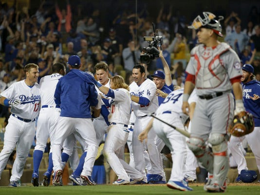 Washington Nationals catcher Wilson Ramos walks off as the Los Angeles Dodgers celebrate after Yasiel Puig's game winning inside the park home run during the ninth inning of a baseball game in Los Angeles, Wednesday, June 22, 2016. (AP Photo/Chris Carlson)
