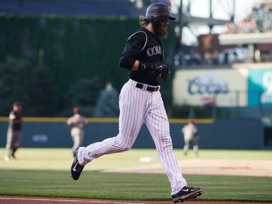 Colorado Rockies' Charlie Blackmon scores on a double hit by Nolan Arenado off Arizona Diamondbacks starting pitcher Zack Greinke in the first inning of a baseball game Thursday, June 23, 2016, in Denver. (AP Photo/David Zalubowski)