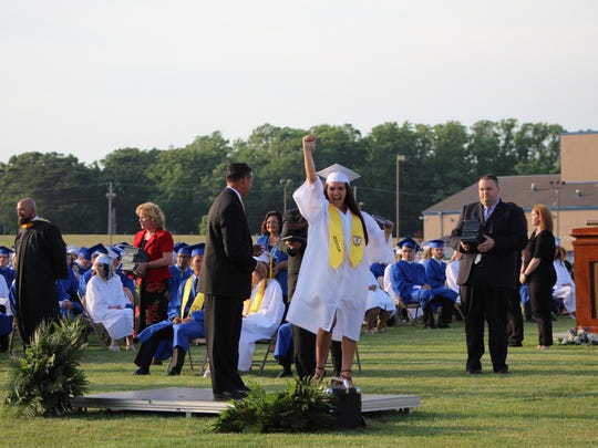 An excited graduate pumps her fist in the air after receiving her diploma.