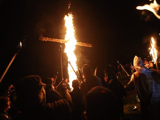 "In this 2016 file photo, members of the Ku Klux Klan participate in cross burnings after a ""white pride"" rally in rural Paulding County near Cedar Town, Georgia."