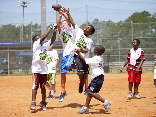 Kids play a game of Moss, going after a football, at Ernie Sims BIG H.I.T.S. Foundation Football and Cheer Camp at Tom Brown Park on Friday.