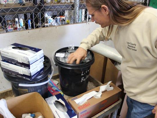 Leon County Hazardous Waste Manager Richard Lobinske sifts through a drum of batteries.