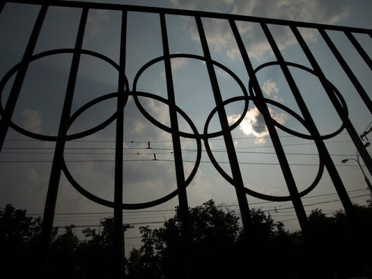 The Olympics rings are seen on a fence in front of the Russian Olympic Committee building in Moscow, Russia, Sunday, July 24, 2016. The IOC has decided against a complete ban on Russian athletes from the Olympics in Rio de Janeiro. The International Olympic Committee says it is leaving it up to global federations to decide which Russian athletes to accept in their sports. (AP Photo/Pavel Golovkin)