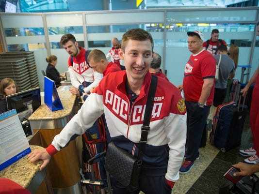 Volleyball player and Russia's National Olympic team member Dmitrij Volkov, center, wait a check in before his team's departure for Rio Olympics, in Moscow, Russia, Thursday, July 28, 2016. At least 105 athletes from the 387-strong Russian Olympic team announced last week have been barred from the Rio Games in connection with the country's doping scandal. (AP Photo/Pavel Golovkin)