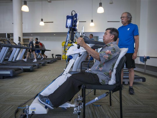 Phoukham Tran uses a functional electrical stimulation therapy bike under the direction of Peter Langston, a medical program instructor at the YMCA Healthy Living Center in Clive on Thursday.