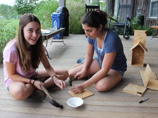 Emily Kaminski, left, and Amelia Charamand work on the construction of the bee houses at Sprout Creek Farm.