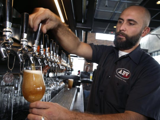 """ABV Social in Wauwatosa offers beers in different sizes, from 4 to 16 ounces. Here, Jamie Shiparski, pours a """"normal"""" 12-ounce beer as well as a 4-ounce sample of HHG (Horseshoes and Hand Grenades) Central, a pale ale from Central Waters Brewing Co."""