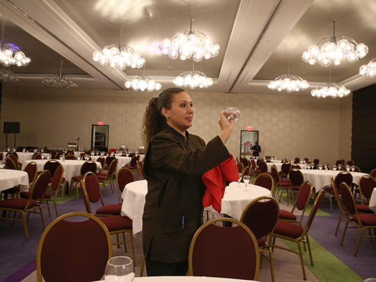 Jill Holton, Banquet Server, polishes glassware as she helps set up the ballroom for a luncheon at the Hyatt Regency Rochester at 125 East Main Street in downtown Rochester Thursday, Oct. 6, 2016.