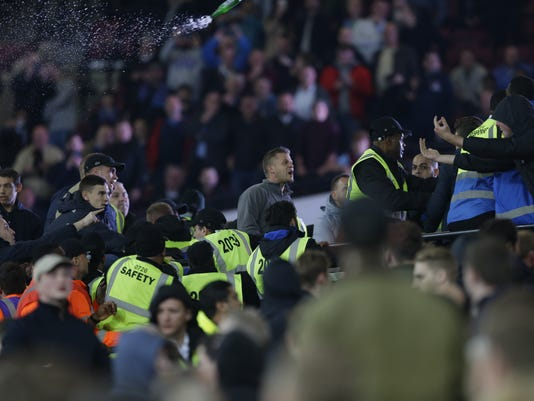 A bottle is thrown as  rival supporters and stewards clash during the English League Cup soccer match between West Ham United and Chelsea at the London stadium in London in London, Wednesday, Oct. 26, 2016. West Ham defeated Chelsea by 2-1. (AP Photo/Alastair Grant)