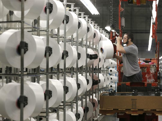 A worker loads spools of thread at the Repreve Bottle Processing Center, part of the Unifi textile company in Yadkinville, N.C.