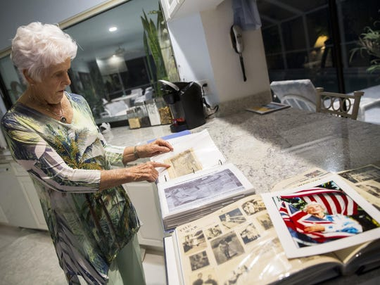Leilani Roberts points to archive photos and articles that she's collected in a scrapbook in her East Naples home on Friday.