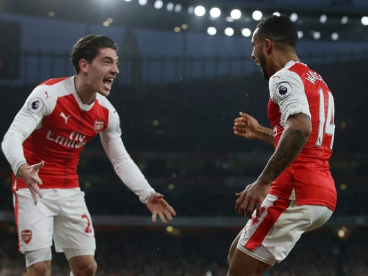 Arsenal's Theo Walcott, right, celebrates after scoring a goal with Arsenal's Hector Bellerin who provided the assist during the English Premier League soccer match between Arsenal and Stoke City at the Emirates stadium in London, Saturday Dec. 10, 2016. (AP Photo/Tim Ireland)