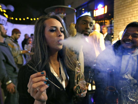 In this 2013 file photo, partygoers smoke marijuana during a Prohibition-era themed New Year's Eve party at a bar in Denver, celebrating the start of retail pot sales.