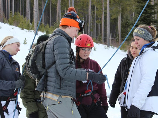Colorado-native, Tony McConnell, an RA at UGF, helps students prepare to climb the Lion's Ridge Tower.