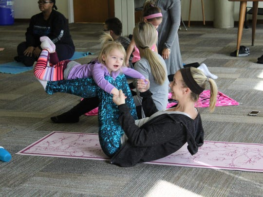 Andrea Bradshaw lifts her daughter, Charlotte, 2, for one of the poses during Toddler Yoga.