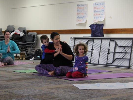 Certified children's yoga instructor Paige Vaccaro and her children, Peter, 6, and Penny, 3, begin the class with a song.