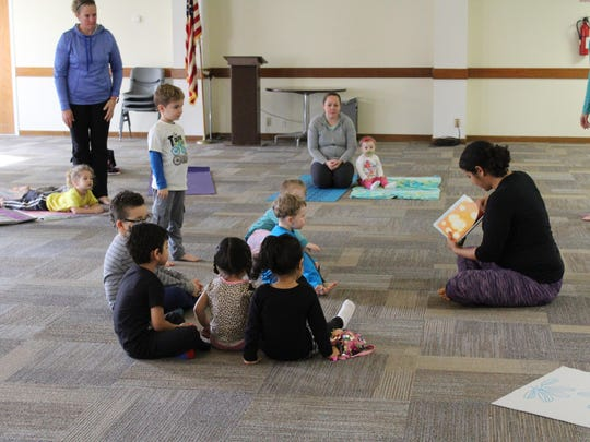 Paige Vaccaro includes a brief story during her Toddler Yoga class on Thursday morning.