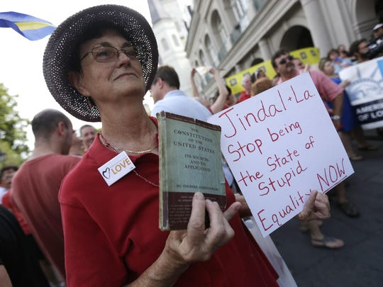 In this June 26, 2013 file photo, Melanie Miranda, of New Orleans holds a copy of the U.S. Constitution during a celebration rally in Jackson Square in New Orleans, after two Supreme Court decisions supporting gay rights were handed down.