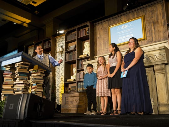 Ruben Renteria, left, introduces his wife, Tania, from right, daughters, Vanessa, 13, and Hannah, 9, and his son, Joshua, 6, during his speech at the 17th annual Florida Celebration of Reading in Bonita Springs on Friday.