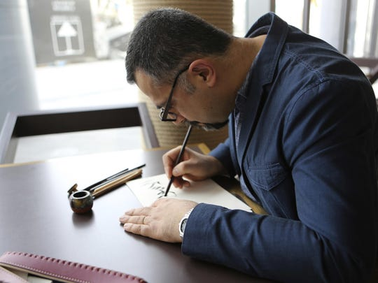 Iraqi calligrapher Wissam Shawkat, who has been featured in the digital edition of Vogue Arabia and created Arabic typography for the print version, works at a cafe in Dubai, United Arab Emirates, Wednesday. Vogue launched its 22nd print edition this month in English and Arabic, targeting a niche audience in the Middle East.